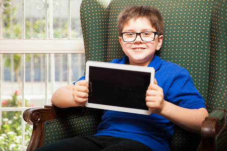 mixed raced: Cute little boy with glasses showing the screen of a tablet computer and smiling Stock Photo