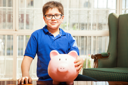 preadolescent: Little kid with glasses holding all of his savings in a piggy bank at home