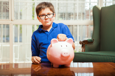 preadolescent: Clever kid with glasses dropping a coin on his piggy bank at home Stock Photo