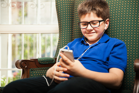 earbuds: Cute Caucasian kid listening to his favorite song using a smartphone and earbuds