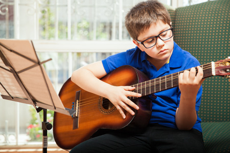 mixed raced: Portrait of a young blond boy with glasses playing the guitar at home