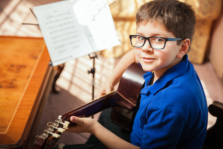 sheet music: Portrait of a young boy with glasses practicing a song during a guitar lesson at home