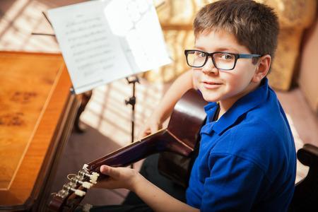 Portret van een jonge jongen met een bril het beoefenen van een nummer tijdens een gitaar les thuis