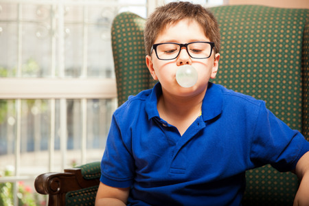 Blond tween with glasses blowing a bubble with some chewing gum at home