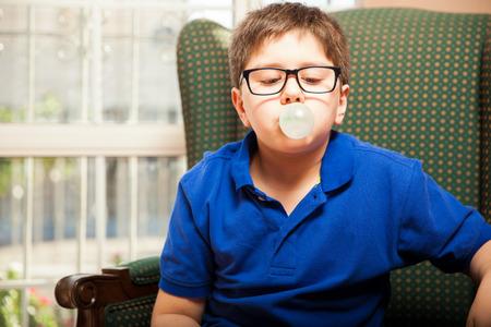 goma de mascar: Entre rubio con los vidrios que sopla una burbuja con un chicle en casa
