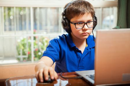 Portrait of a young boy with glasses playing some video games on a laptop computer
