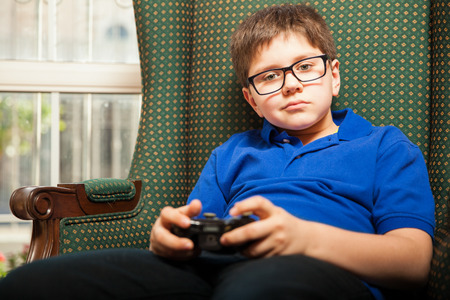mixed raced: Portrait of a cute young boy holding a video game controller at home