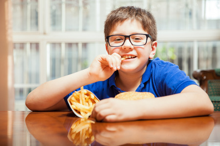 preadolescent: Portrait of a little boy with glasses enjoying some fries and a hamburger at home Stock Photo