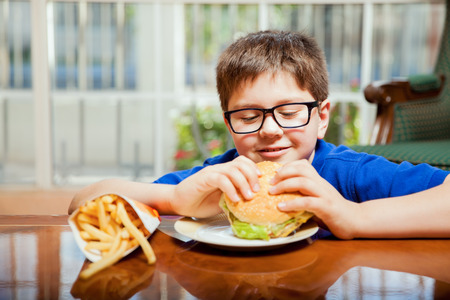 mixed raced: Little boy with glasses about to eat a hamburger with fries at home
