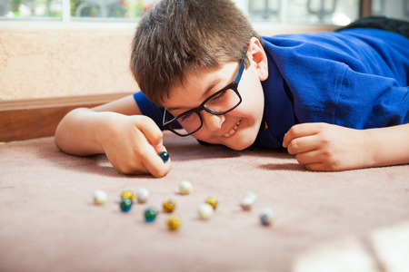 mixed raced: Young white boy playing with marbles and aiming at one at home