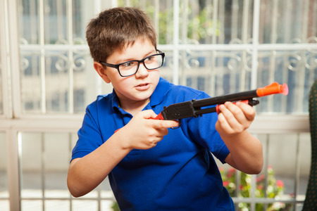 gun room: Funny little boy playing with a toy rifle and about to shoot a dart