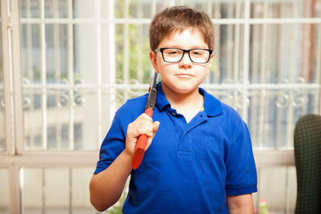 gun room: Portrait of a blond kid with glasses acting all tough with a toy gun Stock Photo