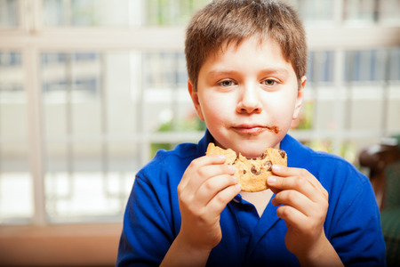 smeared: White kid eating a big cookie and smearing chocolate on his mouth