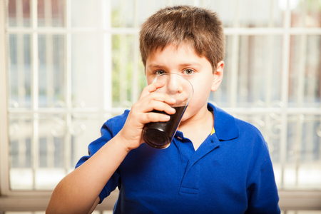 drinking soda: Portrait of a young boy drinking soda from a glass at home