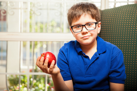 mixed raced: Cute little boy relaxing at home and about to eat a healthy snack Stock Photo