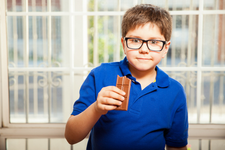 mixed raced: Portrait of a blond kid enjoying a chocolate bar at home
