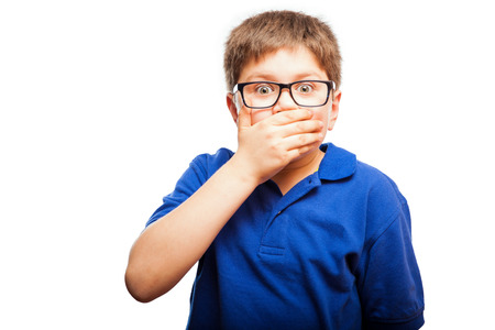 hand on mouth: Little blond boy covering his mouth with a hand as a sign of shock and secrecy Stock Photo