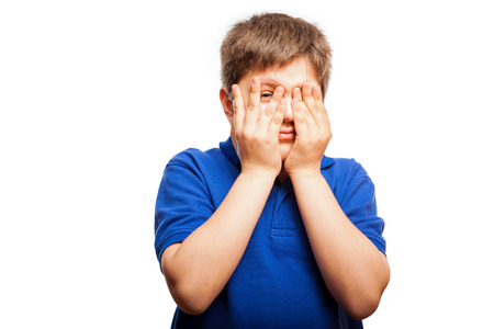 mixed raced: Studio portrait of a blond kid covering his face with both hands and peeking through his fingers to see