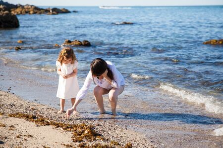 finding love: Young mother and her daughter walking down the beach and looking for sea shells