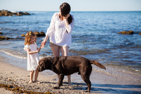 Hispanic young woman relaxing and walking at the beach with her daughter and her dog photo