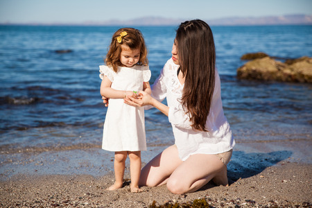 Little Hispanic girl relaxing and hanging out at the beach with her mother photo