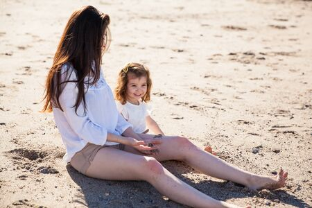 single parent: Pretty young mother spending some time with her little girl at the beach Stock Photo