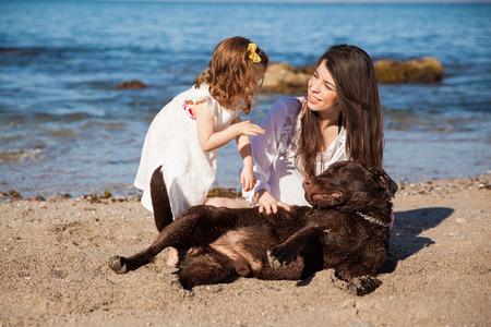madre soltera: Madre soltera y su pequeña hija pasar un rato en la playa con su perro