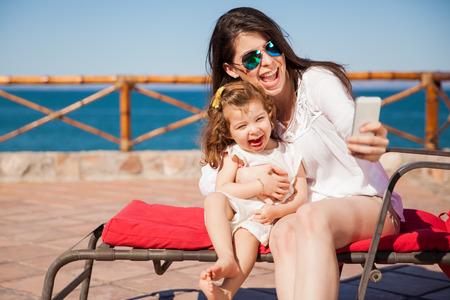 madre soltera: Niña y su mama que un poco de diversión en la playa y tomar un Autofoto con un smartphone