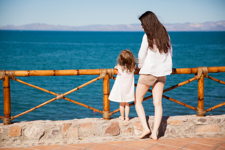 balcony: Rear view of a young woman and her little girl looking at the ocean view from a balcony