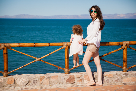 Portrait of a young Hispanic woman and her little daughter spending some vacation time at the beach photo