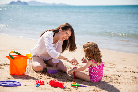 latin mother: Young Latin mother and her little girl using sand to build a castle at the beach