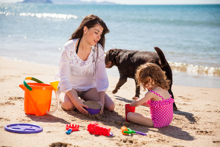 summer dog: Mother and daughter playing together and building a sand castle at the beach Stock Photo