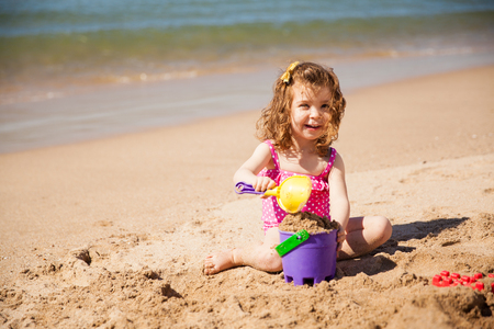 playing in the sea: Portrait of a little white girl playing with buckets of sand at the beach and smiling