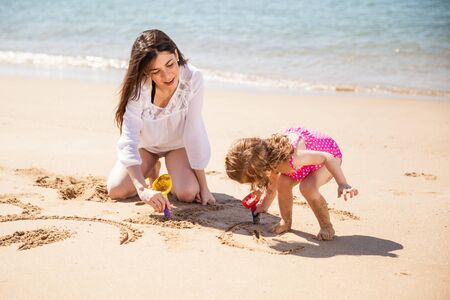 single parent: Little Latin girl and her mom relaxing and drawing on the sand together at the beach