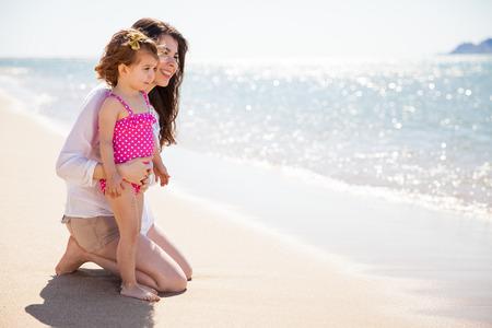 madre soltera: Vista de perfil de una joven madre soltera de pasar un d�a en la playa con su hija Foto de archivo
