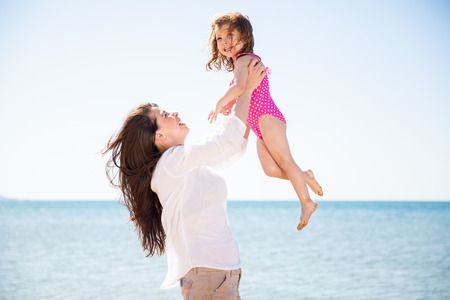latin mother: Happy young Latin mother lifting her daughter up in the air on a sunny day at the beach