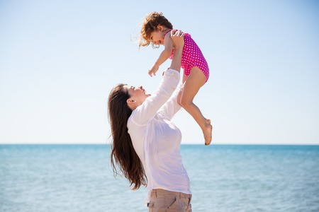 latin family: Profile view of a young mother having some fun at the beach and lifting her little girl up in the air