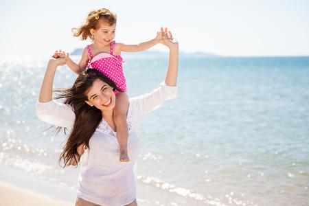 madre soltera: Retrato de una niña bonita de lengüeta monta su madre, mientras que pasar el día en la playa