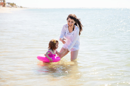 floater: Cute little girl  using a floater in the beach while her mother looks after her