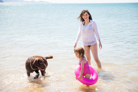 Beautiful young woman enjoying a sunny day at the beach with her daughter and her dog