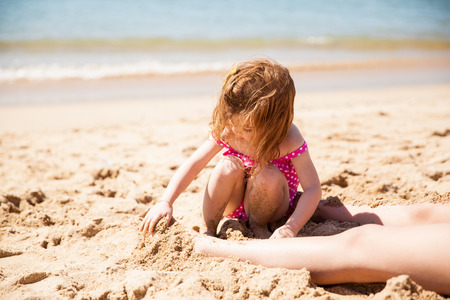 beach feet: Cute little girl sitting at the beach and burying her mother