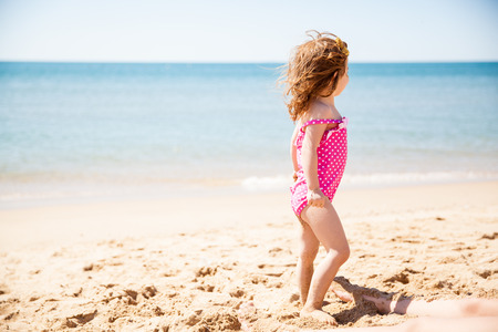 Rear view of a little girl looking curiously at the ocean on a sunny day photo