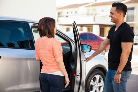 abriendo puerta: Hombre hispánico joven que es un caballero y abrir la puerta del coche para su cita Foto de archivo