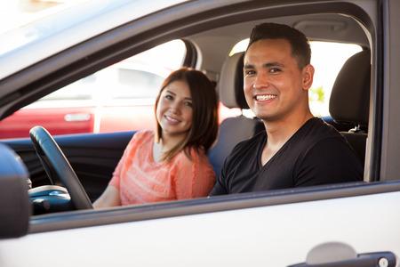 Portrait d'un jeune homme séduisant et sa date de circonscription sur une voiture, aller sur une date