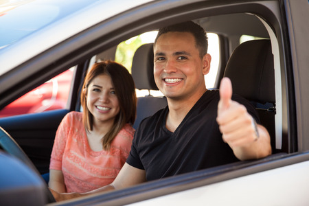 Happy husband and wife enjoying a car ride and giving a thumb up because they really like it Archivio Fotografico