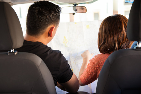 Rear view of a young couple looking for directions on a map while sitting in a car photo