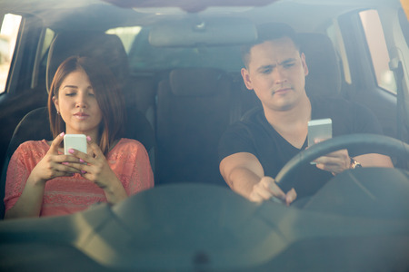 Portrait of a young couple texting and driving together, as seen through the windshield
