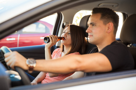 drinking driving: Profile view of a young Latin couple drinking while driving a car