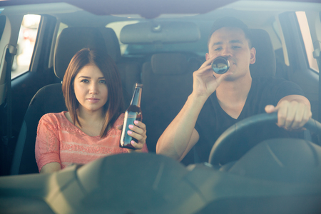 drinking driving: Portrait of a couple of reckless young adults drinking some beer while driving a car