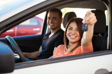 Gelukkig jonge Spaanse vrouw blijkt uit de sleutels van haar nieuwe auto en klaar om weg te rijden met haar partner